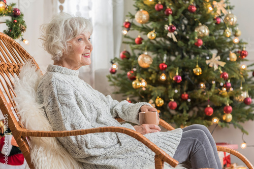 Charming senior lady is holding mug with smile