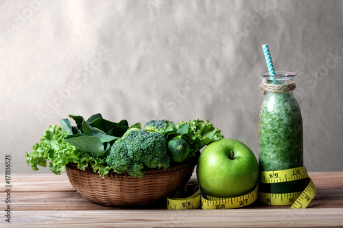 Fotobehang Sap Healthy fresh green smoothie juice in the glass bottle on wooden table with green apple and vegetables basket for healthy detox and diet habits concept