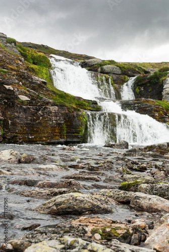 Fotobehang Bleke violet Waterfall in the mountains along the National tourist route Aurl