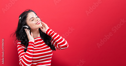 Fotobehang Muziek Happy young woman with headphones on a red background