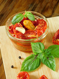 Sun-dried tomatoes with garlic, basil and spices on a wooden board - 171202154