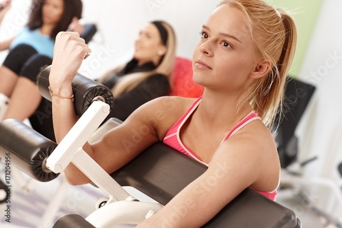 Wall mural Young woman training on weight machine