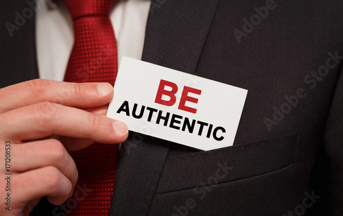 Businessman putting a card with text Be Authentic in the pocket
