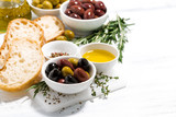 fresh organic olives, spices and bread on white table