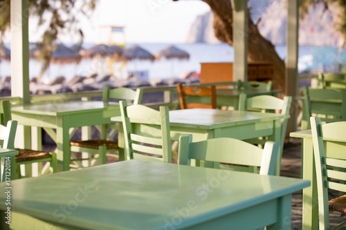Tables and chairs in a street restaurant in Kamari on Santorini