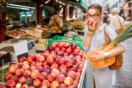 Fotobehang Hoogte schaal Young woman choosing a fresh peach standing with basket at the food market in France