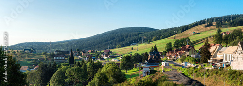 Beautiful panoramic landscape with green grass little houses and blue sky