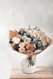 floral composition with roses and mix flowers in glass vase on a gray background. - 171228967