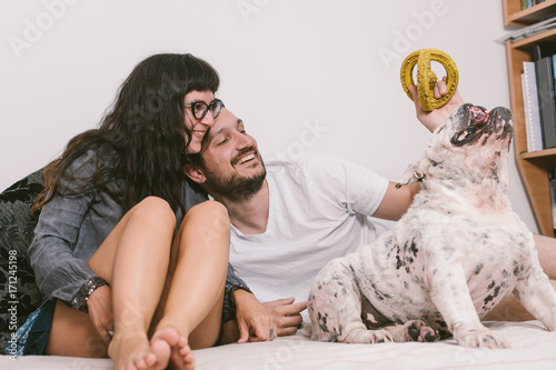 Couple playing with dog in the bed