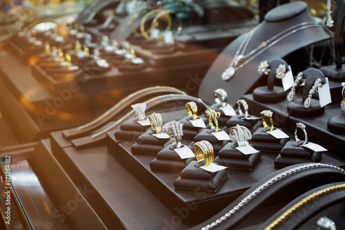 Gold jewelry diamond shop with rings and necklaces luxury retail store window display showcase © Piman Khrutmuang