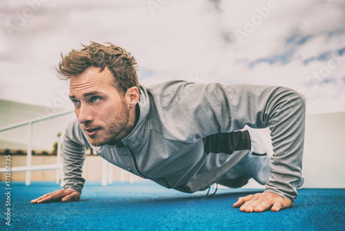 Push-up exercise fitness man training arms muscles at outdoor gym. Male athlete working out with bodyweight floor exercises. - 171268735