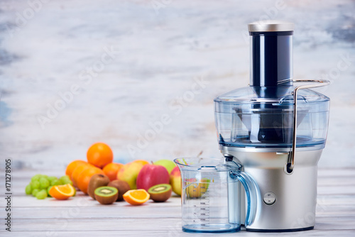 Fotobehang Sap Modern electric juicer and various fruit on kitchen counter, healthy lifestyle detox concept