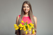 Young happy woman holding basket with yellow tulips. Gray background.
