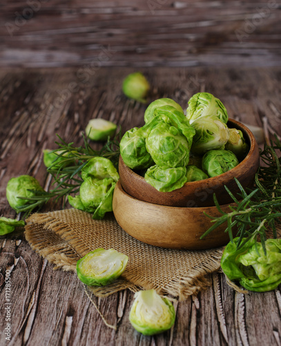 Fotobehang Brussel Green raw Brussels sprouts in wooden bowl , selective focus