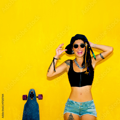 Papiers peints Salon de coiffure Cool Happy girl with dreadlocks, piercings and longboard over colorful yellow wall