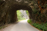 the mountain road passes through a stone tunnel