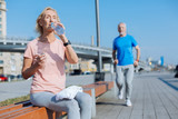Athletic woman drinking water after a morning run - 171308354
