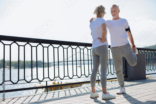 Fit man stretching with the help of his wife