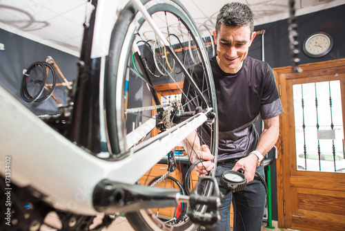 Deurstickers Male involved master is measuring a pressure in tyres of the bicycle in a special workshop