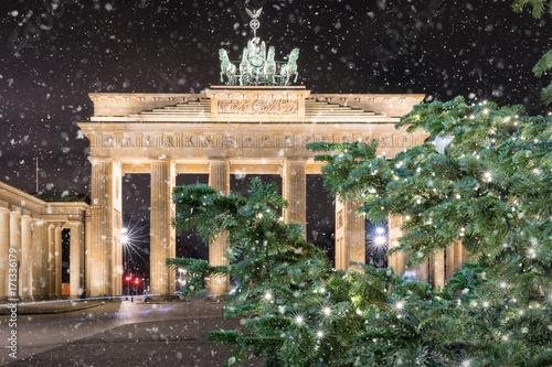 Foto op Plexiglas Berlijn Das Brandeburger Tor in Berlin bei Nacht mit weihnachtlichem Tannenzweig und Schneefall