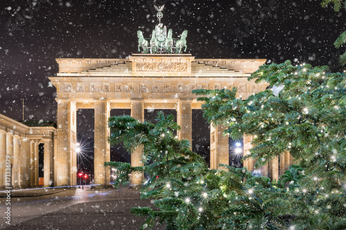 Das Brandeburger Tor in Berlin bei Nacht mit weihnachtlichem Tannenzweig und Sch Poster