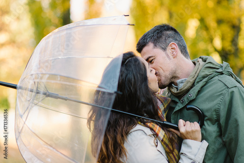 Plakat Lovely young couple kissing in autumn at the park