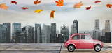 Autumn red toy car with fallen leaves against business district buildings
