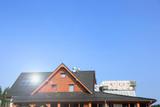 Dach drewnianego budynku z solarami fotowoltanicznymi i systemem wentylacji.