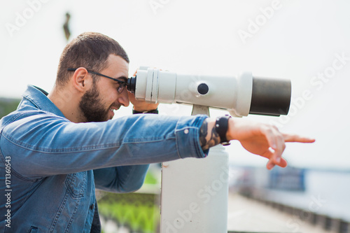 Trendy male person look in binocular telescope points at something