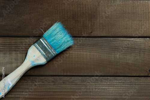 Old brush for paints on a beautiful brown wooden table.