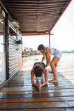 woman fitness instructor assisting young woman in exercise outdoor shot - 171365749