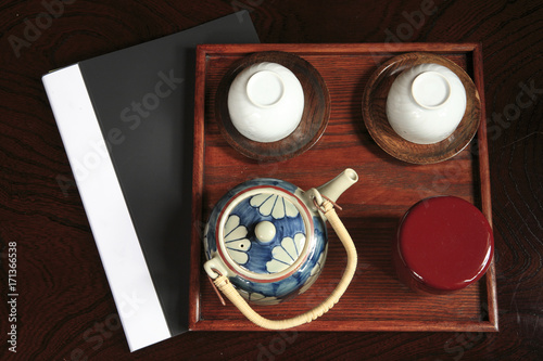 Fotobehang Zen One tea pot, two tea cups, a wooden tray and a document foler in the black background.