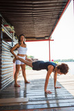 woman fitness instructor assisting young woman in exercise outdoor shot - 171366734