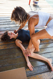 fitness instructor assisting young woman in stretching  exercise outdoor - 171367731