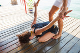 fitness instructor assisting young woman in stretching  exercise outdoor - 171368733