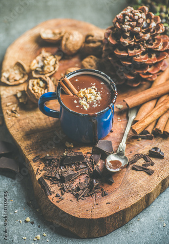 Foto op Plexiglas Chocolade Rich winter hot chocolate with cinnamon sticks and walnut crumb in blue enamel mug on wooden board over grey concrete background, selective focus