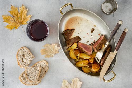 Foto op Plexiglas Steakhouse Slices of beef steak with potatoes in pan with wine