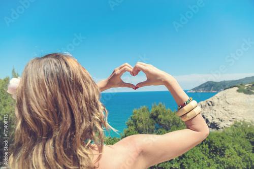 Girl holding a heart shape on the ocean / sea shore.
