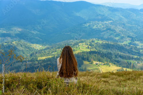 Girl with long hair sitting on a mountainside