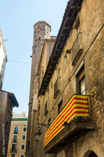 Papiers peints Barcelona Catalan flag, hanging on a balcony, in the Gothic Quarter of Barcelona. Belfry of the Pine Church in the background. Barcelona, Spain.
