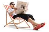 Businessman sitting in a deck chair and reading a newspaper - 171426305