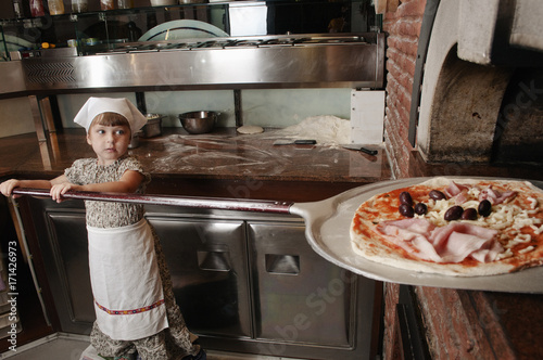 Keuken foto achterwand Pizzeria Baby baker puts pizza into the wood-burning stove