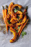Roasted young whole carrot and sliced pumpkin with greens and sea salt on white baking paper as background. Top view with space - 171432962