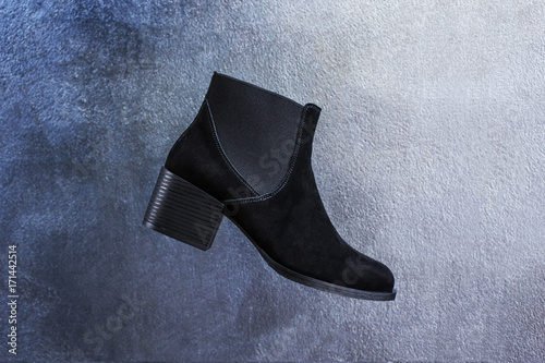 Women's black suede chelsea boots on a shiny decorative background of blue and silver plaster Poster