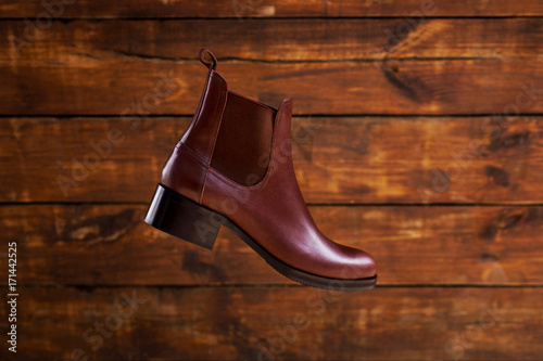 Women's brown leather chelsea boots on a brown wooden background of wooden boards Poster