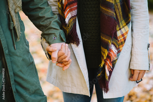 Detail of young couple of lovers  holding hands in autumn at the park. Romantic man and woman in love.