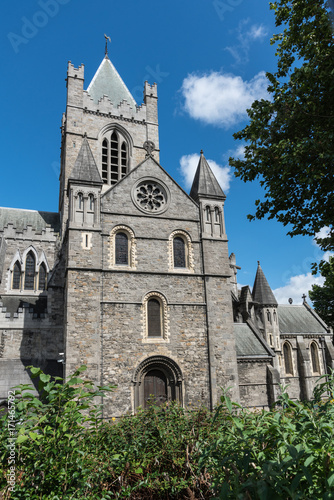 Dublin, Ireland - August 7, 2017: Gray stone bell tower and chancel of Christ Church Cathedral against blue sky with white clouds Poster