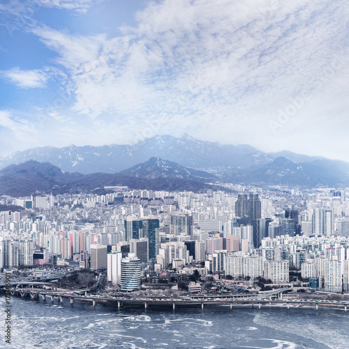 Staande foto Seoel Seoul cityscape, skyline, high rise office buildings in Seoul city, winter daylight Crack on an ice surface of frozen Han river top view in winter, Seoul, Republic of Korea, in fog winter