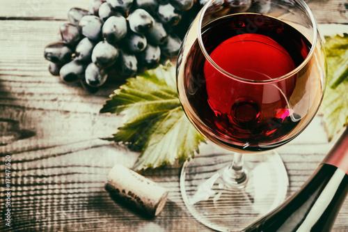 Foto Murales Бокал красного вина крупных планом с виноградом и бутылкой на деревянном столе.