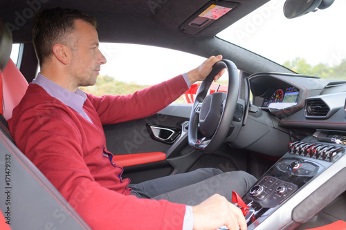 Plakat man sitting and driving in sports car